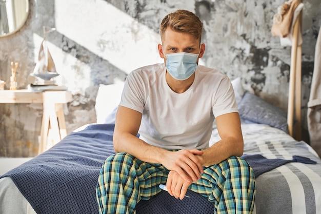 予防措置を主導しながら、自宅で検疫を一人で過ごす、滅菌医療マスクを身に着けている親切な人