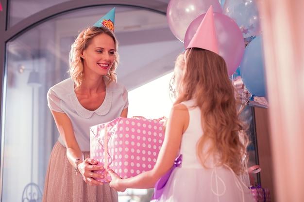 親切なお母さん。彼女に大きな誕生日プレゼントを与えている間彼女の娘に微笑んで傾いている陽気な若い女性