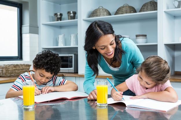 Kind mother helping her children doing homework