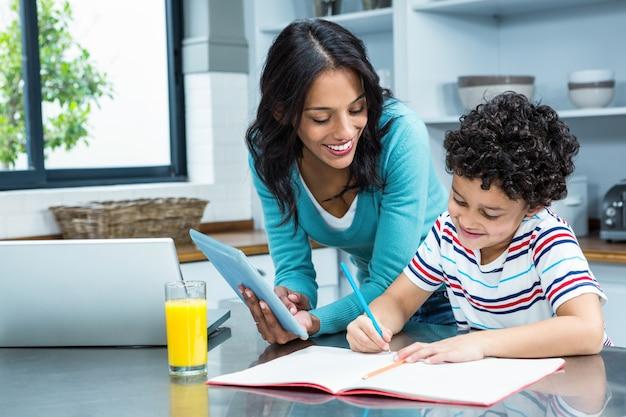 彼女の息子がキッチンで宿題をするのを手助けする親切な母