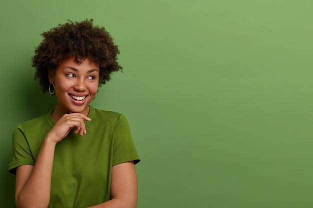 親切な楽観的な若いアフリカ系アメリカ人女性は脇を向いて、あごの下で優しく手を保ち、素晴らしいイベントを想像し、カジュアルな緑のtシャツを着て、屋内でポーズをとり、広告にぴったりの空白スペースを作ります