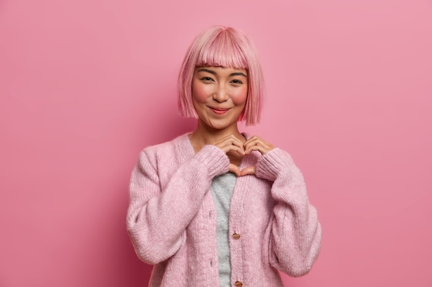Kind positive amiable asian woman with bob hairstyle, makes heart shape gesture