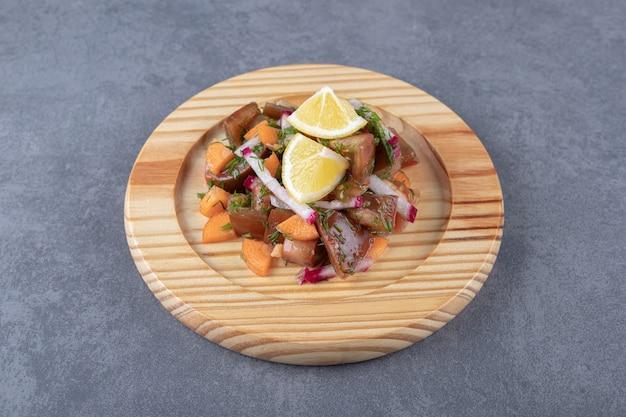 Una specie di verdura nel piatto di legno, sulla superficie di marmo.