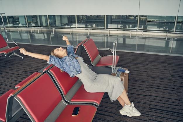 Добрая женщина поднимает руки, сохраняя улыбку на лице во время ожидания на посадке