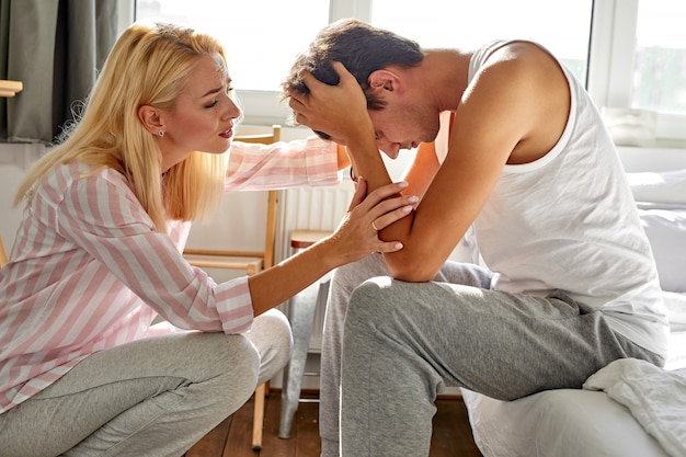 Добрая женщина поддерживает своего мужа дома, женщина разговаривает с мужчиной, сидящим с опущенной головой, в спальне.