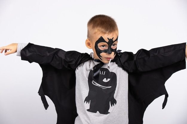 A kindergarten boy in a bat costume on a halloween party with a lady. sweets and holidays for children.
