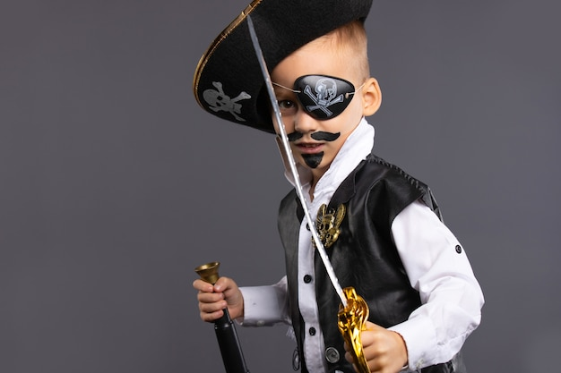 A kindergarten boy in a pirate captain costume with a painted face, sword and telescope. happy halloween.