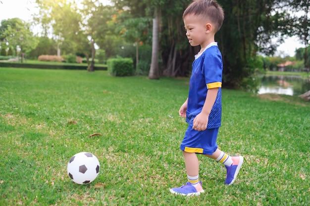 Kindergarten boy in soccer uniform is playing football