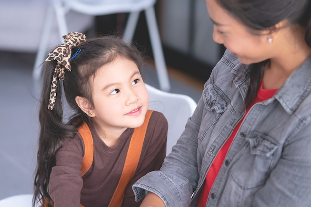 Kindergarten is talking smiling to female teacher