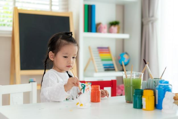 幼稚園の学校の女の子が自宅のリビングルームでアクリル絵の具でプラスター人形を塗装します。