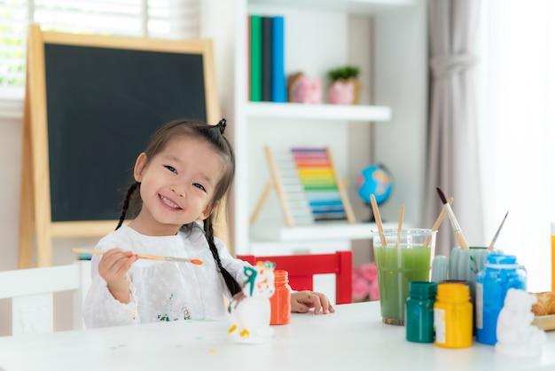 アクリル絵の具で石膏人形を描く幼稚園の学校の女の子