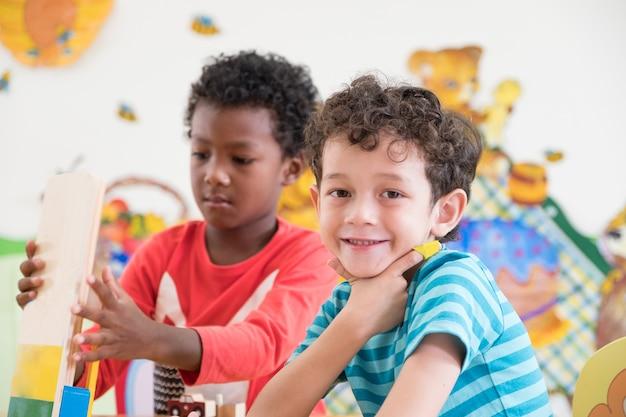 幼稚園の学生は幼稚園のインターナショナルで遊び場でおもちゃを演奏すると笑う