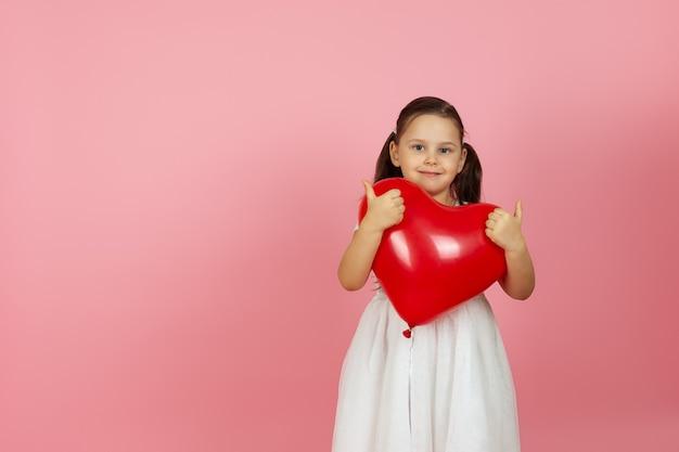 엄지 손가락을 포기하는 심장 모양의 빨간 풍선을 들고 흰 드레스에 친절하게 마음을 다한 소녀