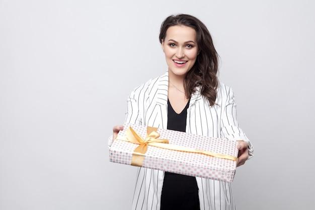 Доброта привлекательная молодая брюнетка женщина в белом с черными линиями пальто стоя и давая подарок с желтым бантом и зубастой улыбкой, глядя в камеру. крытый, изолированный, студийный снимок, серый фон