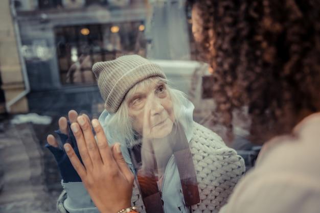人への優しさ。ホームレスの女性を見ながら窓の近くに立っている楽しいアフロアメリカ人女性