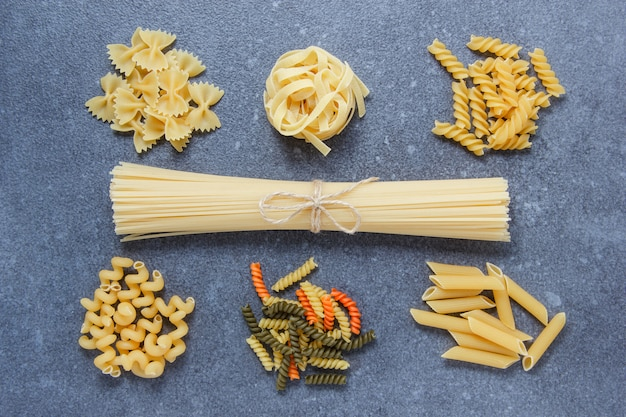 Kinds of macaroni pastas with spaghetti top view on a gray surface