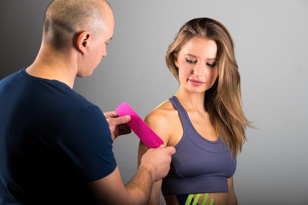 젊은 여자의 어깨에 kinesio 테이프
