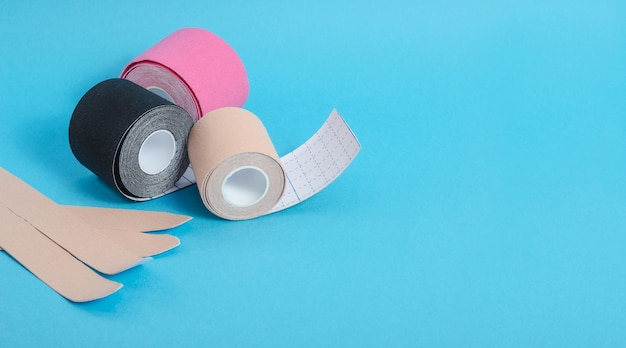 Kinesiological multi-colored tapes for fixing muscles during sports and after injuries on a blue background with a copy space. kinesiological taping of athletes.