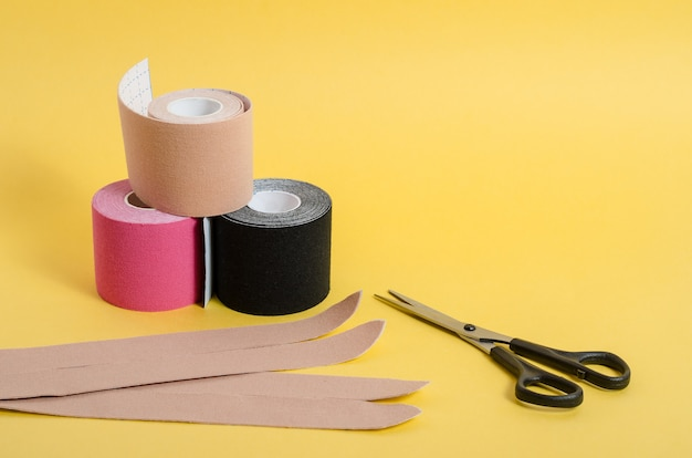 Kinesiological multi-colored tapes for fixing muscles during sports and after injuries on a yellow background with copy space. kinesiological taping of athletes.