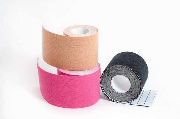 スポーツ中や白い表面の怪我の後に筋肉を固定するための運動学的マルチカラーテープ。アスリートの運動学的テーピング。
