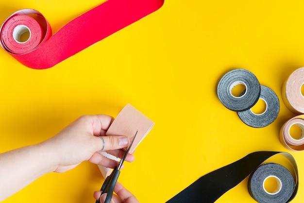 운동 요법 테이핑 처리 공정 단계. 여성의 손은 노란색의 적용을 위해 빨간 테이프를 자르고 있습니다.