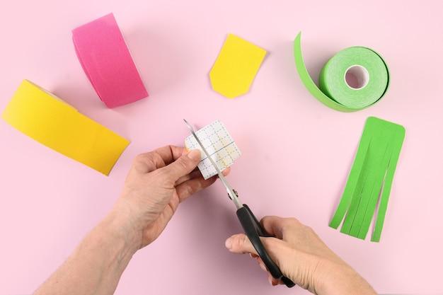 キネシオロジー テーピングの女性がピンクのテープをカットし、ランタン本体の形を整え、リンパの流れを整える