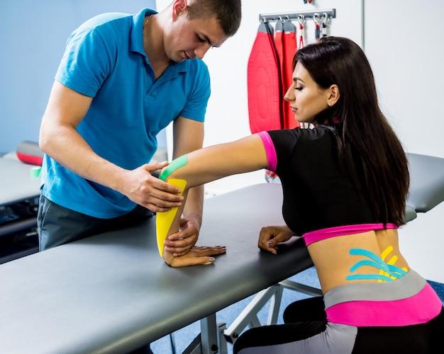 운동 요법. 물리 치료사 젊은 아름 다운 여자의 척추, 손 및 큐빗에 테이프를 적용.