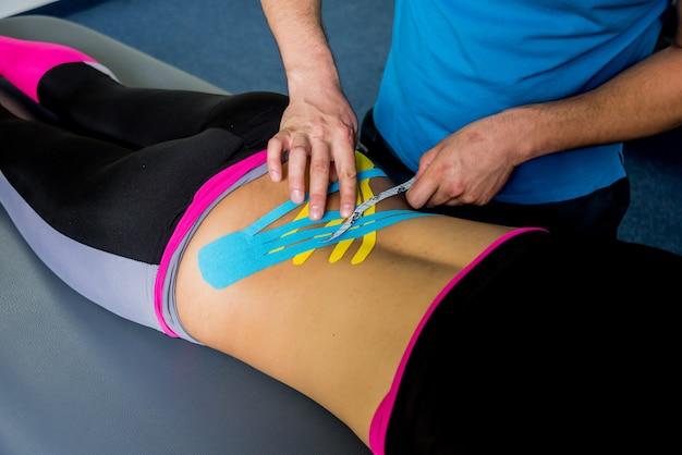 キネシオテーピング。理学療法士が若い美しい女性の背骨にテープを貼り付けます。