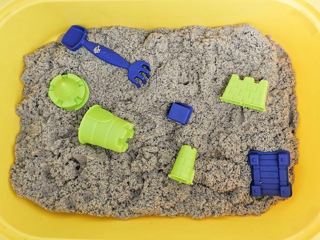 黄色い容器におもちゃが入った自然な色のキネティックサンド。細かい運動技能のための子供との教育ゲーム。