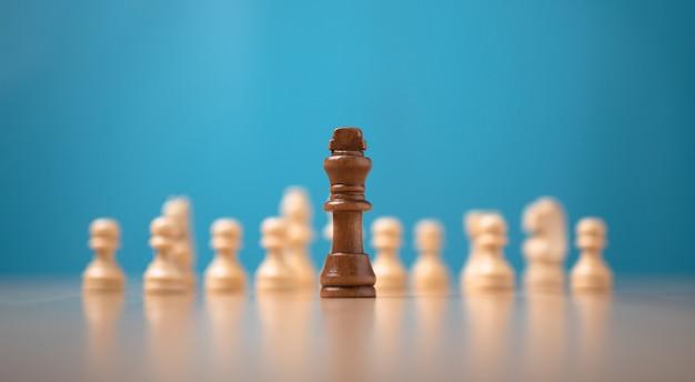 白いチェスの前に立っているキングブラウンチェス、競争の挑戦の概念