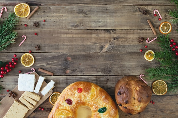 King cake and panettone on a wooden base with christmas decorations. dessert of kings and panettone. typical food.