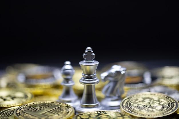 킹 체스와 다른 하나는 금 비트코인 암호 화폐 배경 위에 서 있습니다.