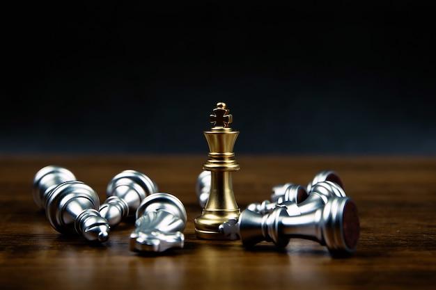 Король шахмат стоит с падающими шахматами.