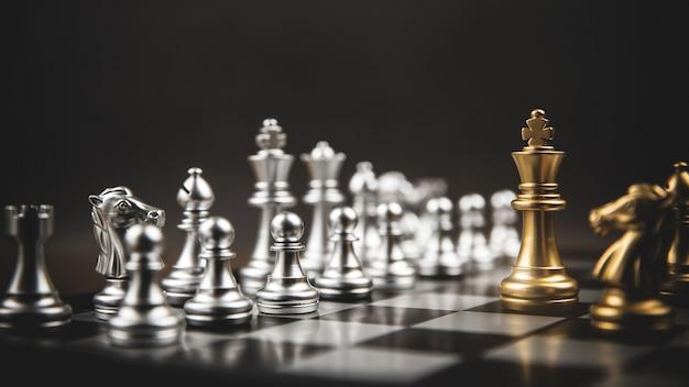 Король золотых шахмат стоя противостоит серебряной шахматной команде