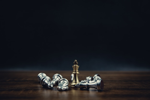 King golden chess standing of the falling silver chess with dark background.