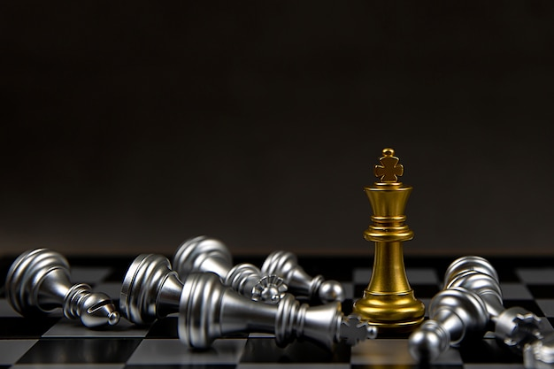 The king golden chess standing in the middle of the falling silver chess.