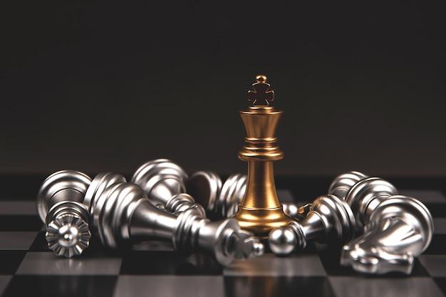 Король золотые шахматы стоя падающих серебряных шахмат с темным фоном.