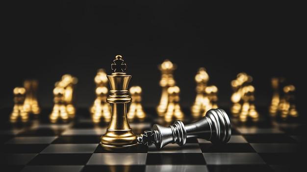 Король золотого шахматиста стоящего падающего серебра на шахматной доске понятия лидерства