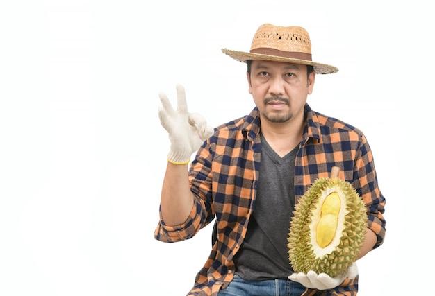 タイ、モントンドリアンを保持しているアジア人男性農家の果物の王様と白で隔離okサイン手を表示