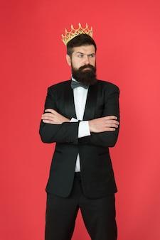 Король стиля. жених человек в свадебном костюме. стиль большого босса. официальное мероприятие. корона короля. бородатый мужчина в смокинге и галстуке-бабочке. эгоист. бизнесмен в смокинге и королевской короне. формальная одежда мужского модного стиля.
