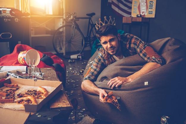 Король вечеринки. молодой красавец в пластиковой короне лежит на фасоли с пиццей