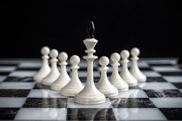 The king and pawns on a chess board on a dark background.