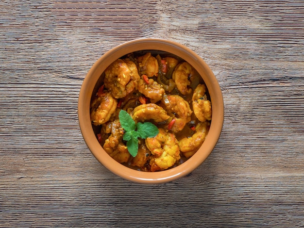King prawn masala in a clay bowl. traditional indian cuisine