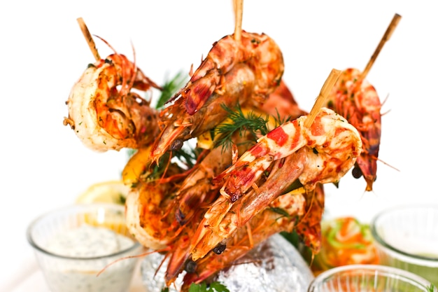 King prawns cooked on wooden skewers. serving with sauces and herbs on a white plate.