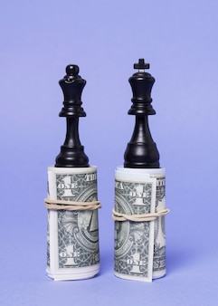 King and queen pieces of chess standing on equal amount of money