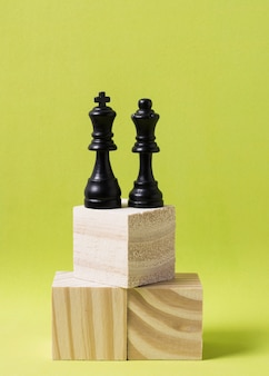 King and queen pieces of chess on wooden cubes at same height