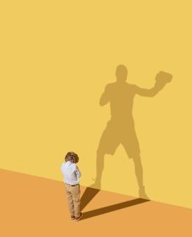 Il colpo del re per vincere. futuro campione. infanzia e concetto di sogno. immagine concettuale con bambino e ombra sulla parete gialla dello studio. il ragazzino vuole diventare un pugile e costruire una carriera sportiva.