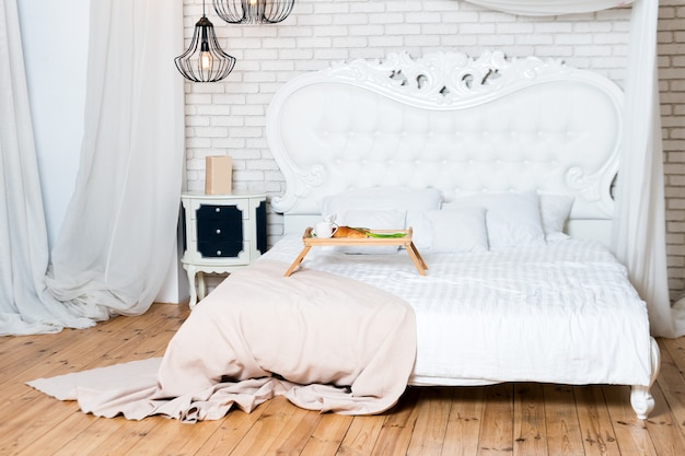 Кровать размера «king-size» в апартаментах-лофте, завтрак в постель, поднос с кофе, круассанами и цветами, медовый месяц, раннее утро в отеле.