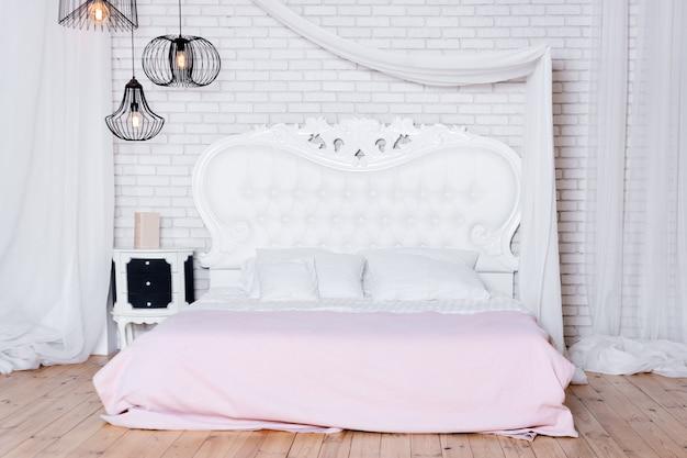 Большая двуспальная кровать в квартире-лофте, спальня в стиле лофт с белым дизайном.