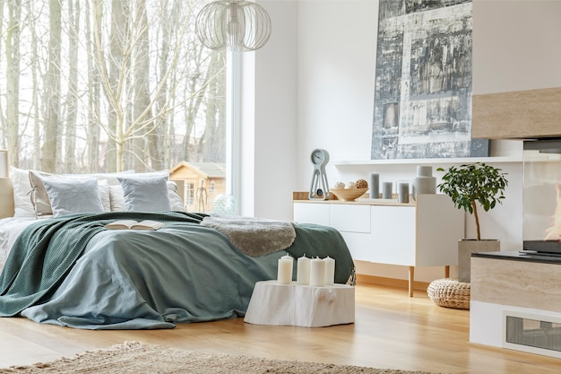 King-size bed with a cozy bedding, large window, shelves and a painting in a spacious bedroom interior with fireplace